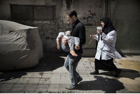 A Syrian man carries his wounded daughter