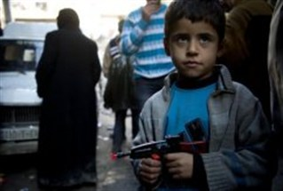 Syrian boy holds toy pistol in Aleppo, where jihadists take over army base