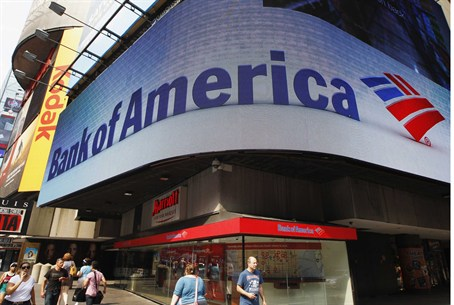 Tourists walk past a Bank of America banking