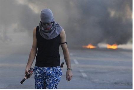 Bahraini protester west of Manama holds fireb