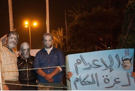 Protesters wear masks of Morsi and other Egyp