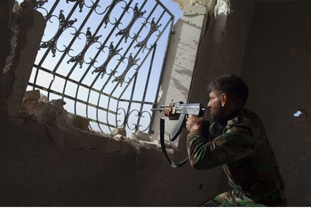 Rebel fighter aims his weapon towards Syrian