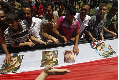 Syrians carry flag with pictures of Syria's a