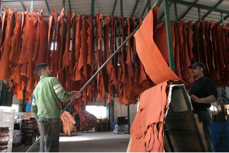 Workers prepare leather at PA factory in Hevr