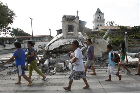 Residents walk past the ruins of a church in