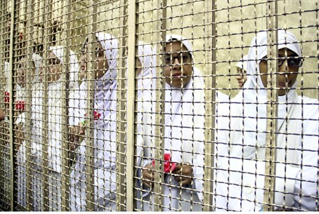 The defendants in a holding cell during their