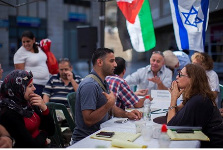 Palestinian and Israeli people discuss at a p