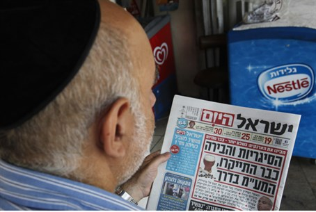 Man reads Israel Hayom