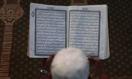 Muslim reads Koran (illustration)