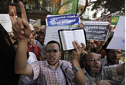 People shout and hold slogans in front of the U.S. embassy during a protest in Cairo