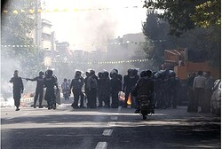 Iranian riot police stand next to a waste bin set on fire by protesters