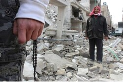 A resident holds prayer beads near buildings, damaged by missiles fired by a Syrian fighter jet near